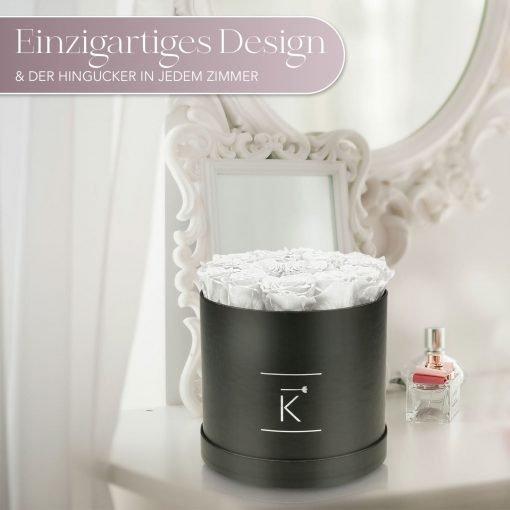 Große runde Rosenbox mit weißen Infinityrosen, die auf einem Schminktisch steht
