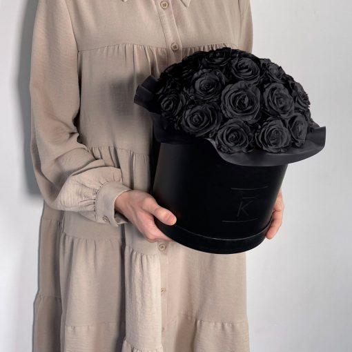 Gorgeuos Rosenbox rund mit schwarzen Infinityrosen wird von einer Frau in ihren Händen gehalten
