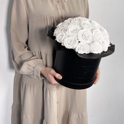 Gorgeuos Rosenbox rund mit weißen Infinityrosen wird von einer Frau in ihren Händen gehalten