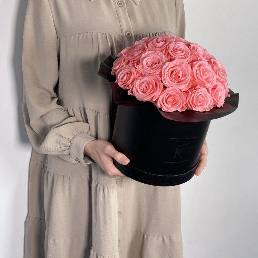 Gorgeuos Rosenbox rund mit pinken Infinityrosen wird von einer Frau in ihren Händen gehalten