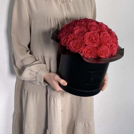 Gorgeuos Rosenbox rund mit roten Infinityrosen wird von einer Frau in ihren Händen gehalten