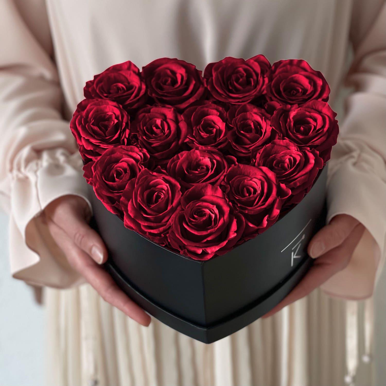 Rosenbox schwarz in herzform mit dunkelroten Infinityrosen wird von Frau in den händen gehalten