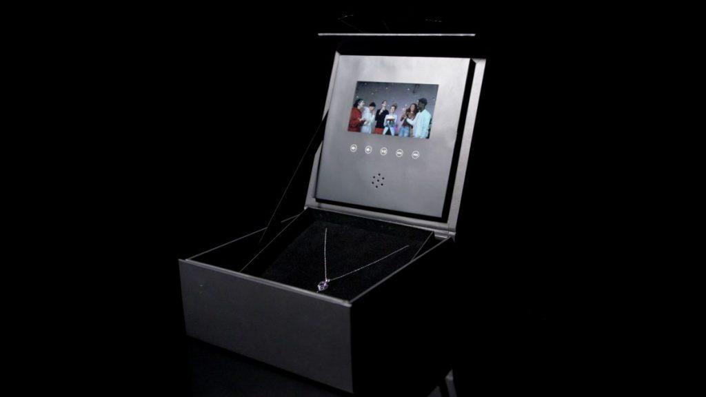 Geöffnete Geschenkbox mit Video, in der ein Schmuckstück liegt