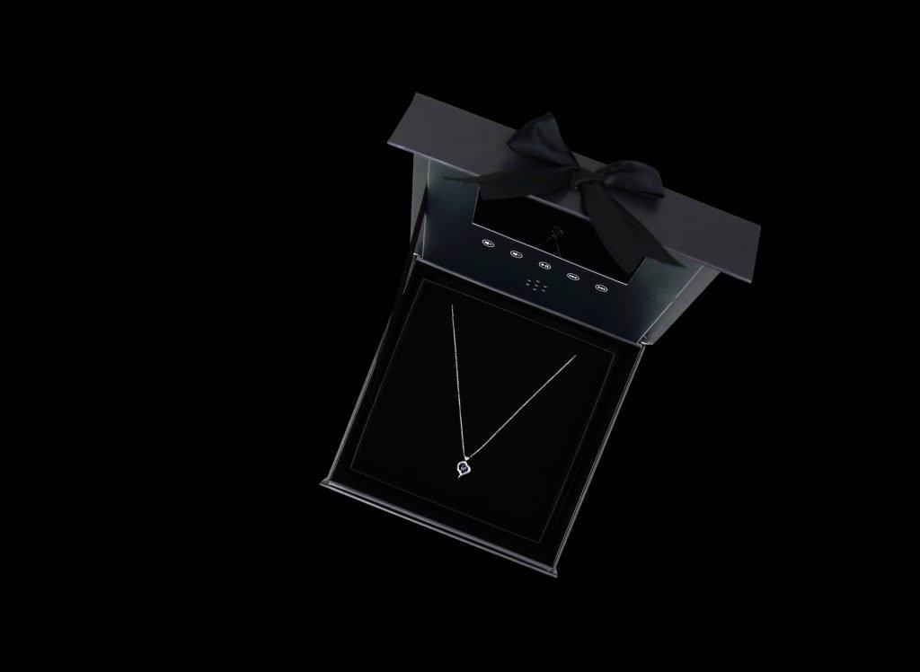 Geöffnete Geschenkbox mit Video und einem Schmuckstück