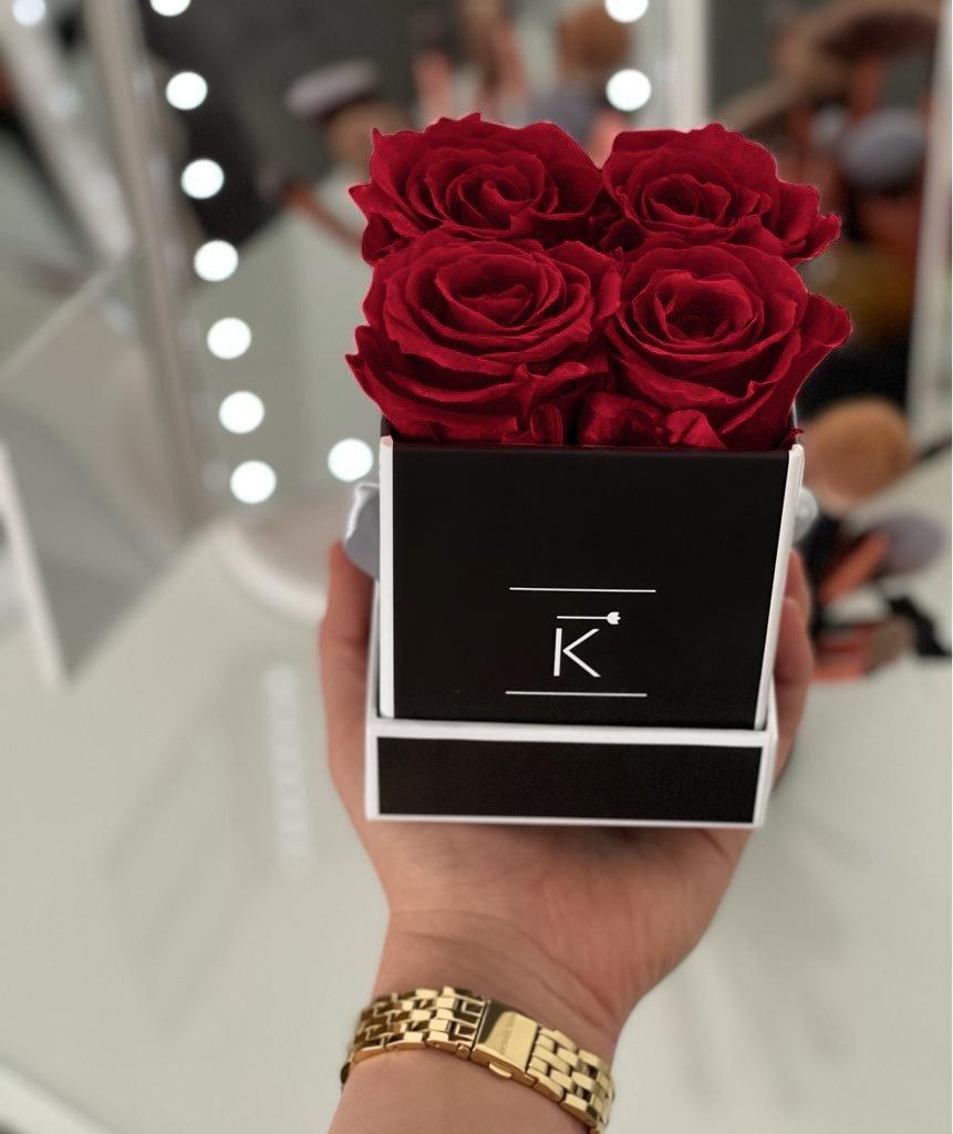Kleine Rosenbox schwarz weiß mit dunkelroten Infinityrosen wird von einer Frau in der Hand gehalten