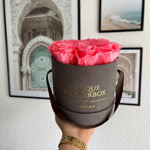 Runde Rosenbox mit pfirsichrosanen Infinityrosen, graues Samtfinish und Henkel zum Tragen, wird von einer Frau in der Hand gehalten