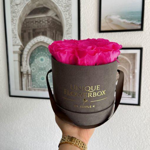 Runde Rosenbox mit pinken Infinityrosen, graues Samtfinish und Henkel zum Tragen, wird von einer Frau in der Hand gehalten