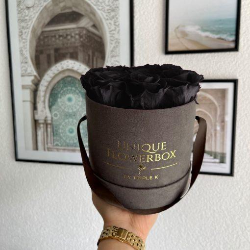 Runde Rosenbox mit schwarzen Infinityrosen, graues Samtfinish und Henkel zum Tragen, wird von einer Frau in der Hand gehalten