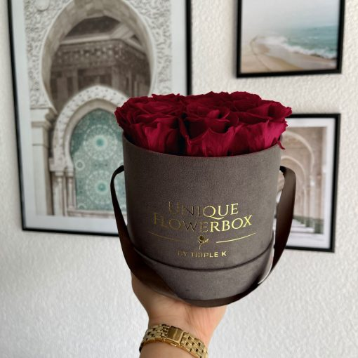 Runde Rosenbox mit roten Infinityrosen, graues Samtfinish und Henkel zum Tragen, wird von einer Frau in der Hand gehalten