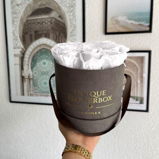 Runde Rosenbox mit weißen Infinityrosen, graues Samtfinish und Henkel zum Tragen, wird von einer Frau in der Hand gehalten